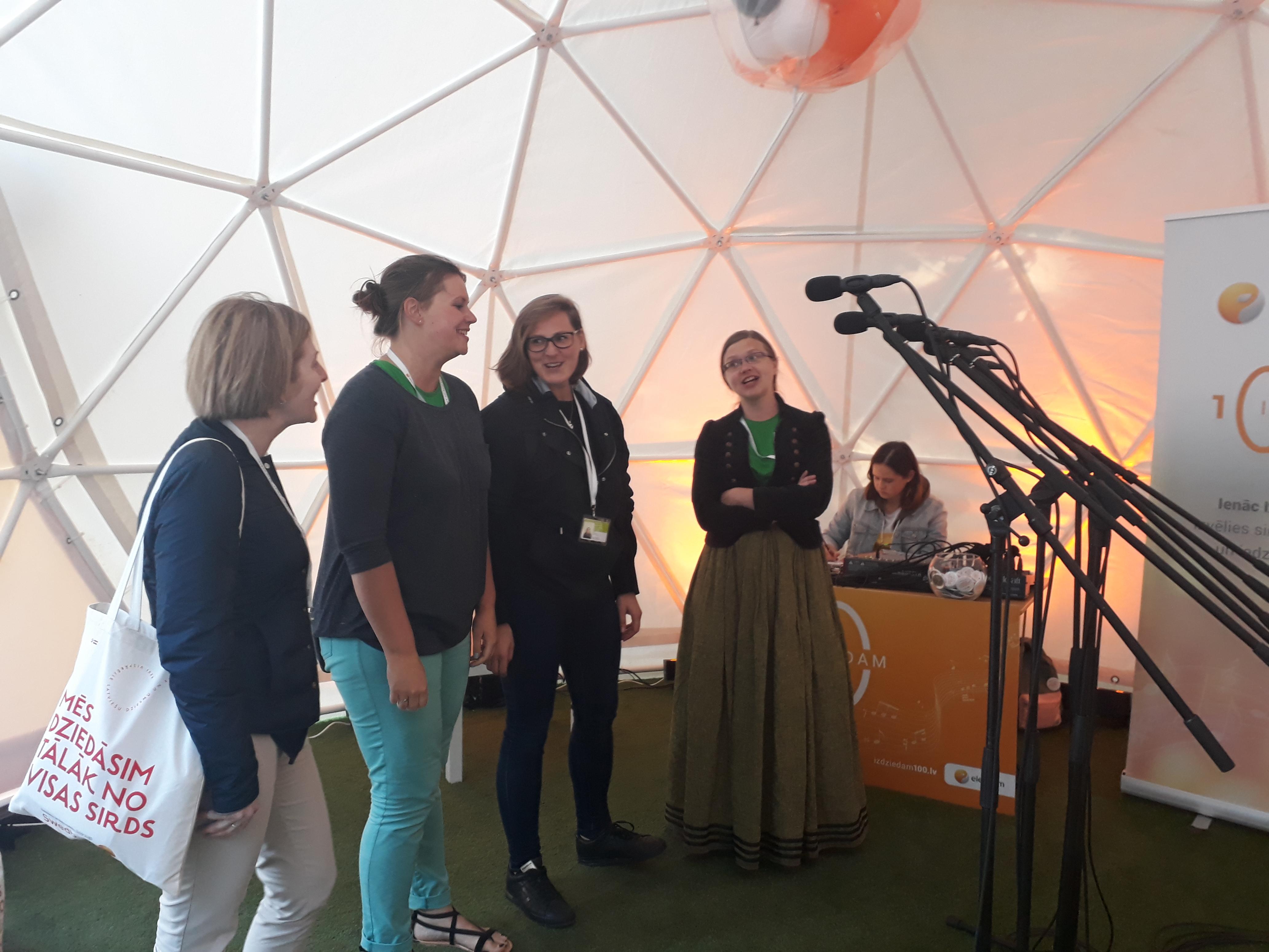 Mēģinājumu starplaiki tika izmantoti lietderīgi - kāda paguva aizskriet uz mājām, lai pabarotu savu pāris mēnešu veco zīdainīti, cita  nodarbojās ar rokdarbiem, steidzot pabeigt  līdz nosēguma koncertam pēdējās detaļas jaunajam tautastērpam, vēl citas turpat Electrum  teltī piedalījās kopīgas  dāvanas radīšanā  Latvijai 100- gadē - iedziedot dziesmu. Attēlā - 1. soprāna meitenes, iedziedot savu  sveicienu Latvijai;